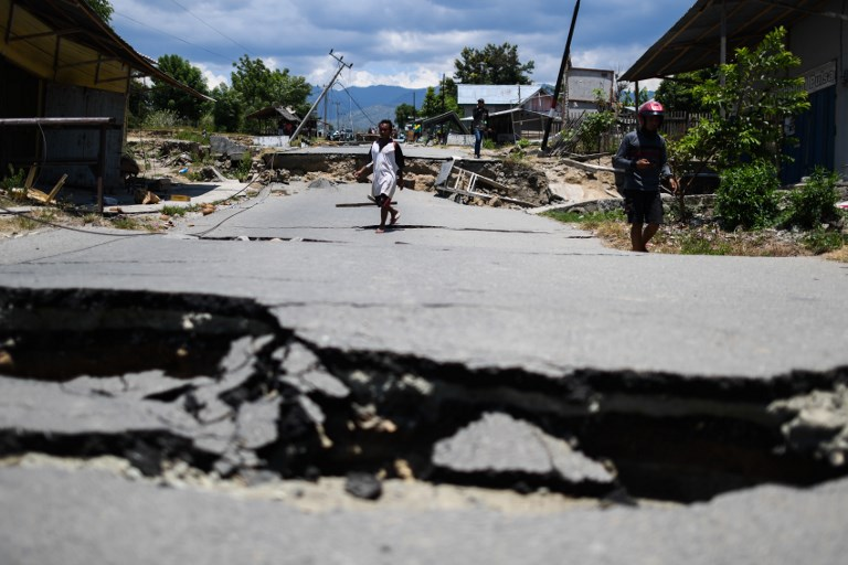 Survivors walk on a damaged street outside Palu in Indonesia's Central Sulawesi