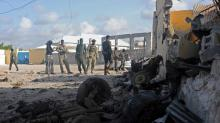 Somali soldiers stand next to the site where Al Shebab militants carried out a suicide attack against a military intelligence base in Mogadishu on June 21, 2015.