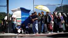 Central American migrants queue at a border connecting Guatemala and Mexico while waiting to cross into Mexico, in Talisman, Mexico.