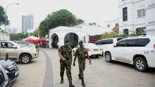 Sri Lankan soldiers walk outside the prime minister's official residence in Colombo.