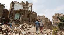 People walk past a house destroyed by an air strike in the old quarter of Sanaa, Yemen August 8, 2018.