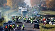 People wearing yellow vests, a symbol of a French drivers' nationwide protest against higher fuel prices, block the Paris-Brussels motorway in Haulchin, France.