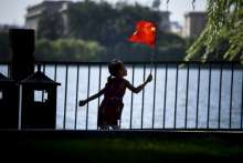 A girl holds a Chinese national flag as she visits a park in Beijing