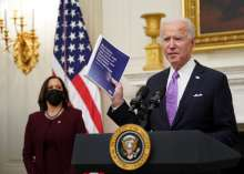 US President Joe Biden speaks about the Covid-19 response as US Vice President Kamala Harris looks on before signing executive orders